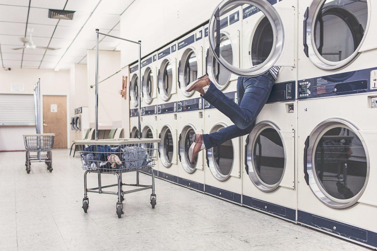 person dives into laundromat dryer