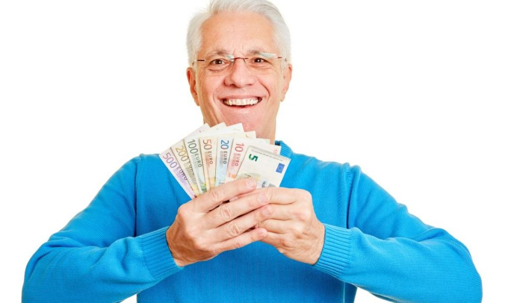 a happy grandpa showing money that he saved while renting on a storage facility