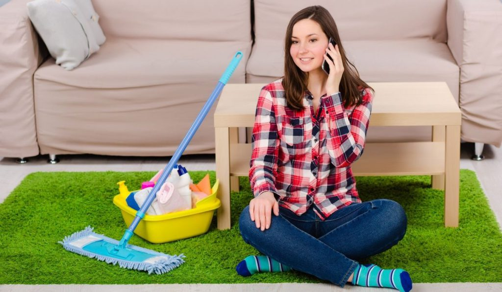 girl on the phone while resting after cleaning her place
