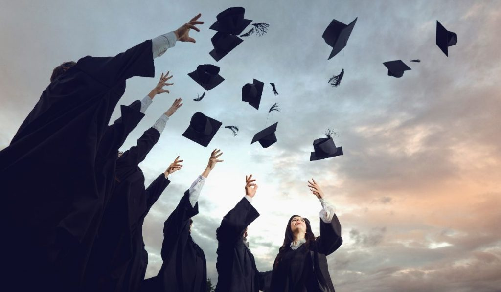 graduates throwing their hats up in the sky