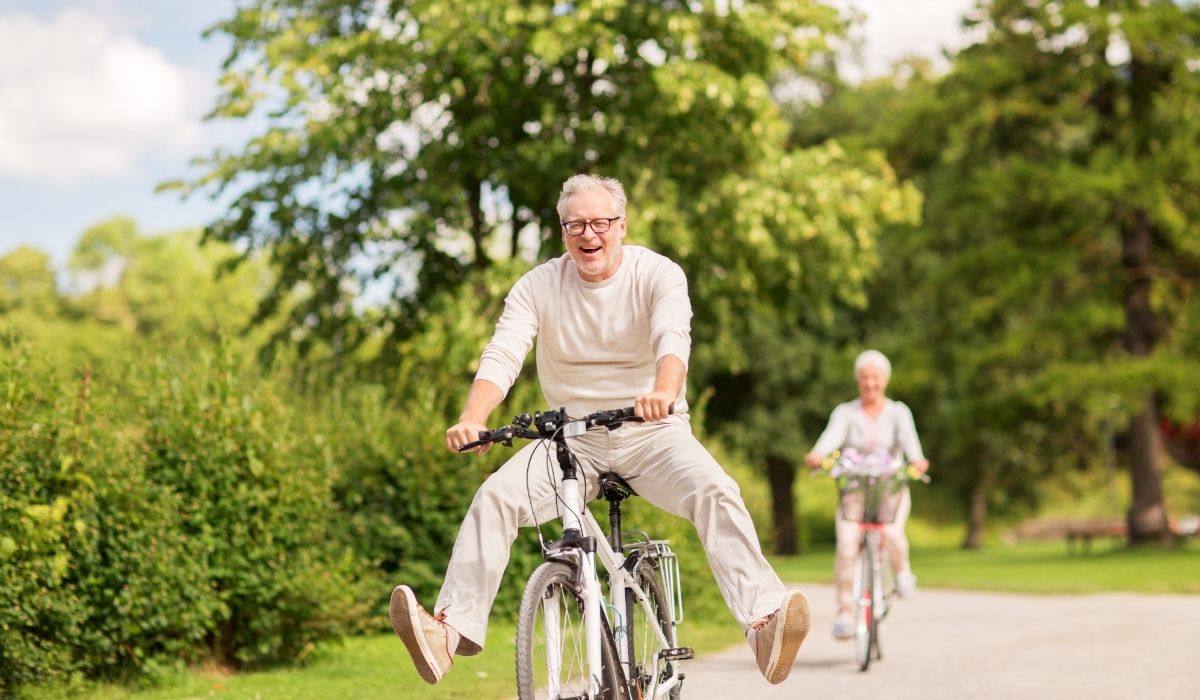 happy senior couple riding a bicycle in the park and enjoying life