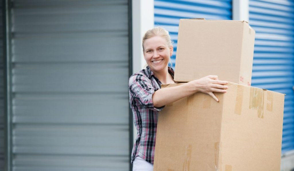 woman holding boxes renting a storage unit for the first time